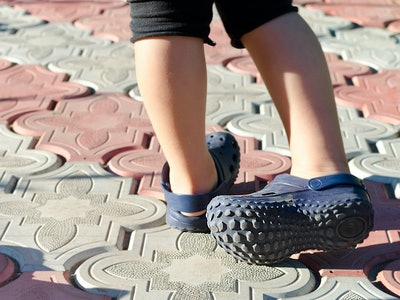 Small boy wearing blue rubber Crocs sandals outdoors.