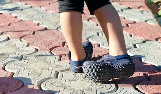 Small boy wearing blue rubber Crocs sandals outdoors.