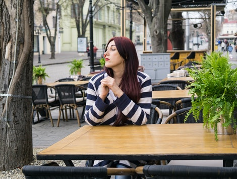 Young lady with long hair sitting alone in cafe