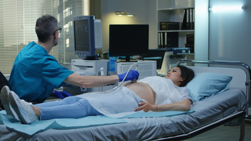 Medium shot of a male doctor preparing a pregnant female patient for ultrasound examination