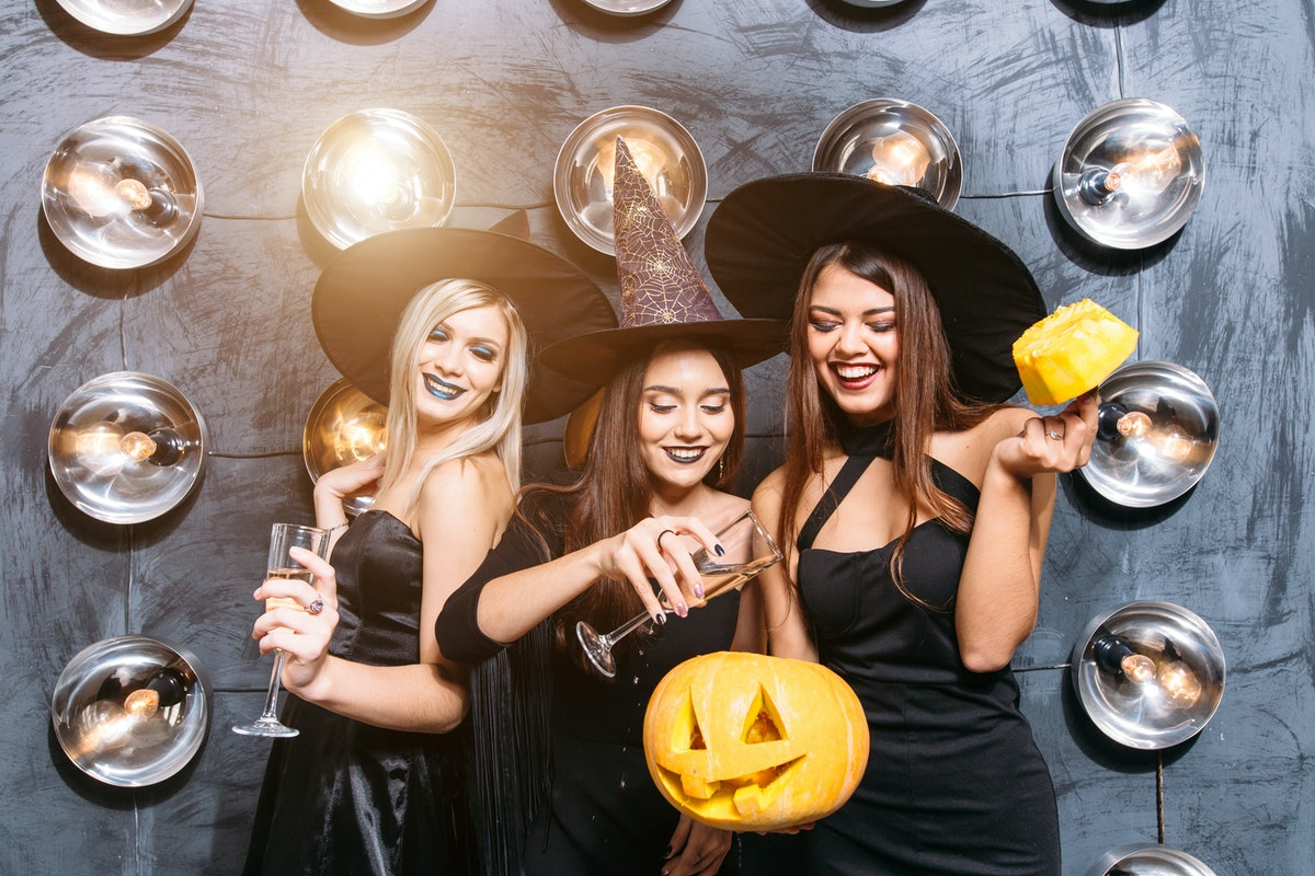Picture of three emotional young women in halloween costumes on party with pumpkin.