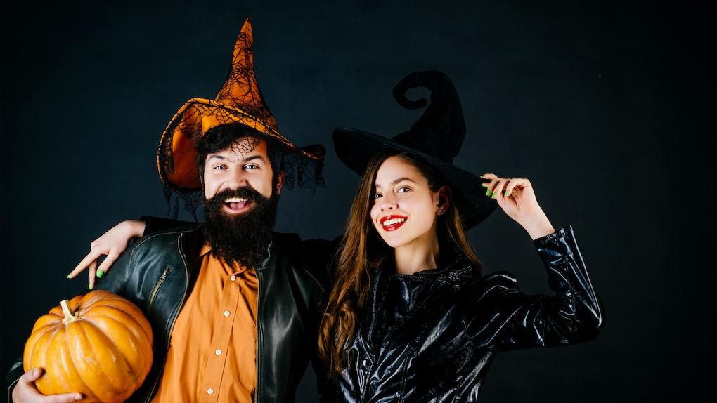 Best friends celebrated Halloween. Portrait of happy young couple in Halloween with pumpkin. Retro Halloween couple romancing