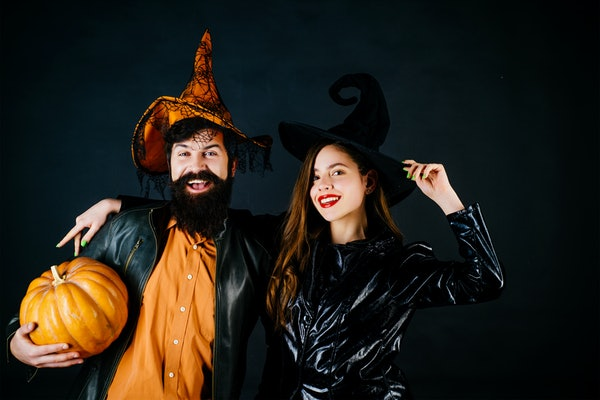 Best friends celebrated Halloween. Portrait of happy young couple in Halloween with pumpkin. Retro Halloween couple romancing