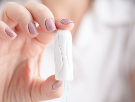 Girl holding tampon during the monthly cycle. Young woman hands holding menstruation cotton tampon