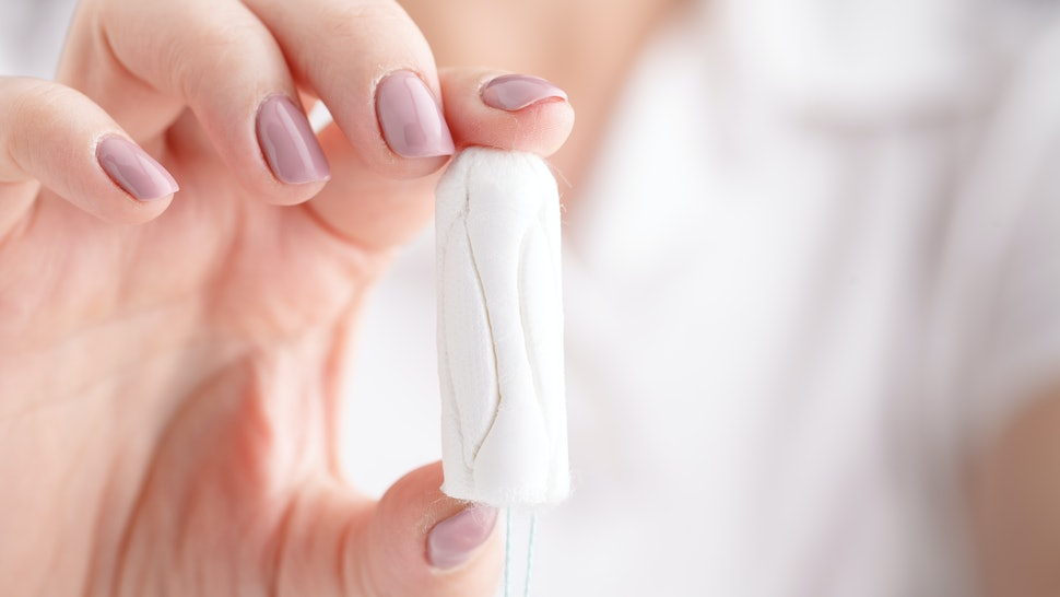 woman holding a tampon