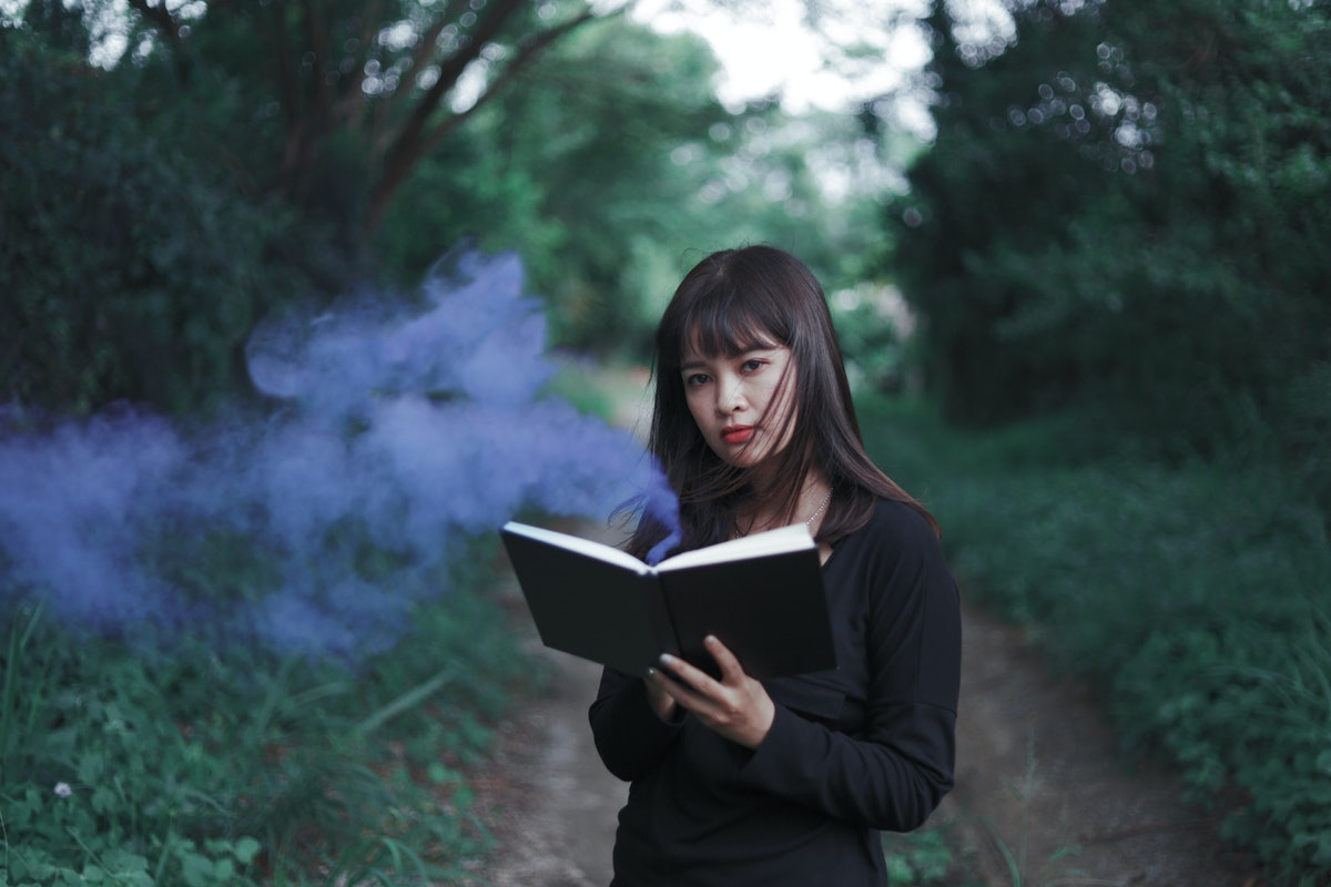 Portrait Asian woman in black dress holding a little notebook in hands, witch-hunt before Halloween night concept.