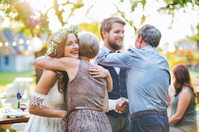 Guests congratulating bride and groom at wedding reception outside in the backyard.