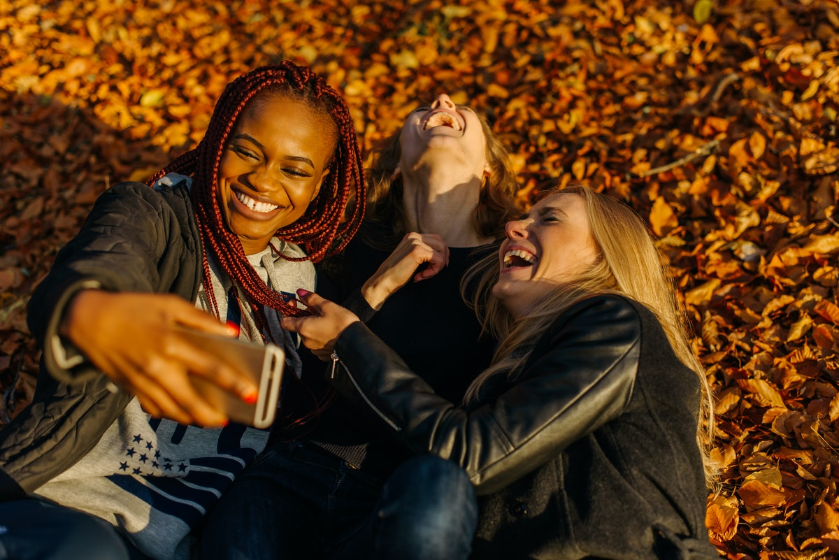 very happy female friends making funny selfie in autumn park. Cute girls with different colored skin. Female lying in yellow leaves and making smiling faces at camera. Sunny autamn day