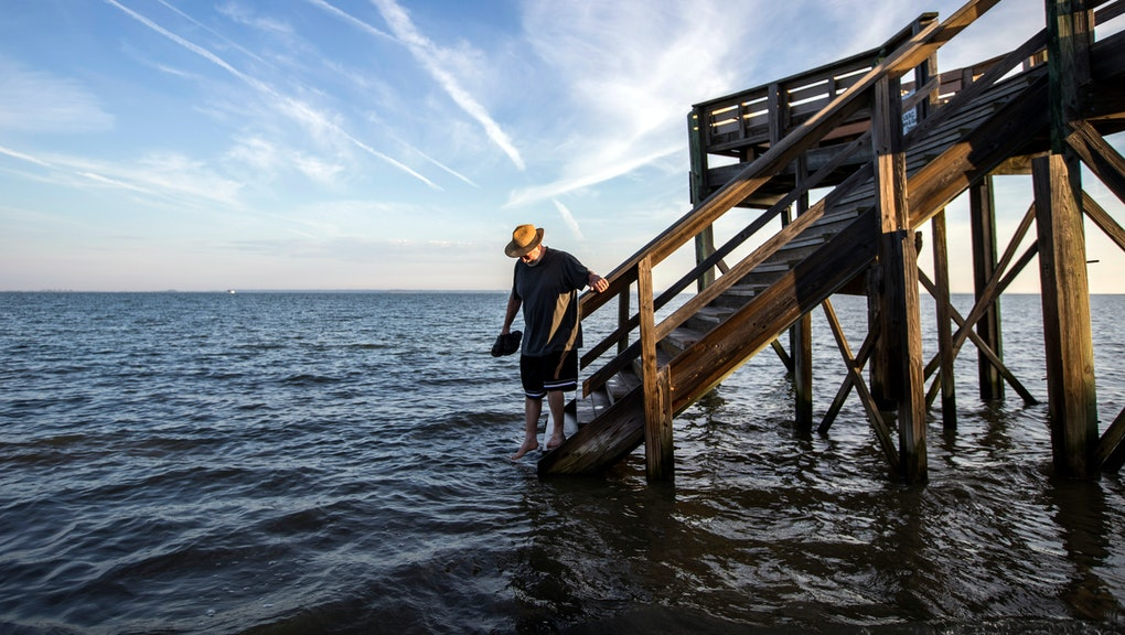Visiting the area for the first time, 64-year-old Fran Glod of Oswego, N.Y, walks down the steps to the beach which is covered by a king tide high tide, on Tybee Island, Ga. The annual king tide is the year's highest astronomical tide when the alignment of the full moon cause higher than normal tides along the coast