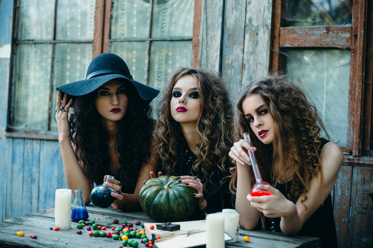 three witches are sitting at the table and prepared the potion on the eve of Halloween