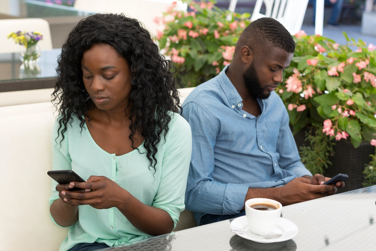 Smarthone addiction. Obsessed couple with their mobile phones ignoring each other sitting in cafe