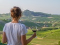 handsome girl holding a glass of red wine looking amazing green vineyards in the italian region of P...