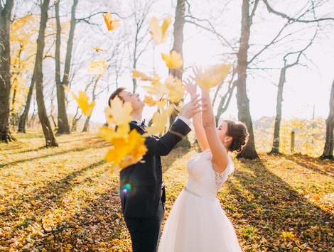 The autumn composition of the happy newlyweds throwing up the yellowed leaves in the park.
