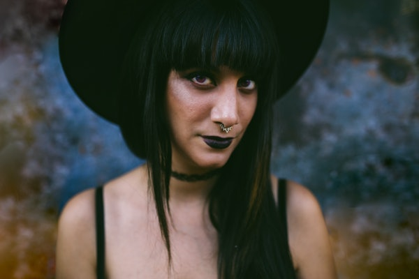 Young happy Halloween witch woman looking to the camera. Beauty Witch lady with black mouth in the darkness, wearing a witch hat. Serious girl with costume and Halloween make up. Dark background.
