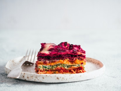 Vegetable Packed Rainbow Lasagne on craft plate.Ideas and recipes for healthy vegetarian dinner or lunch. Lasagne with beetroot,pumpkin,mushrooms,ricotta,spinach,mozarella on white table. Copy space