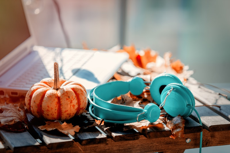 Orange pumpkin, headphones and leaves near laptop computer on a table. Autumn season time