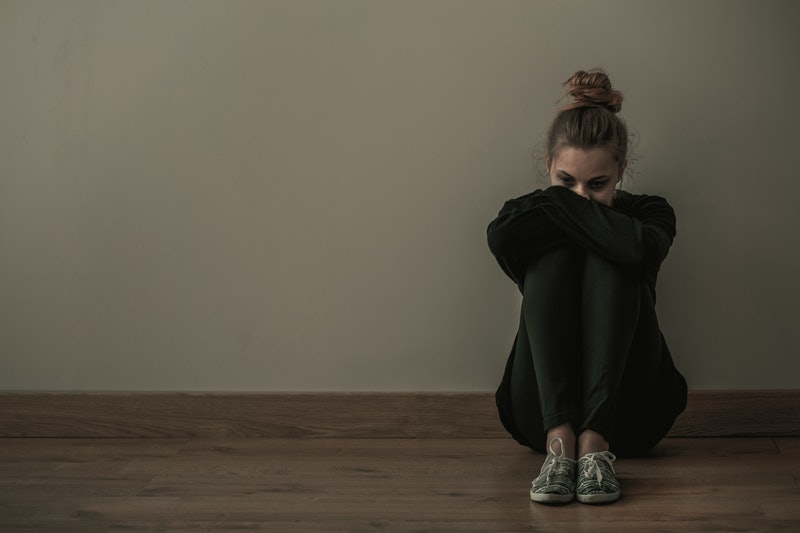 Young woman with anxiety disorder wearing dark clothes sitting on the floor, copy space on empty wall