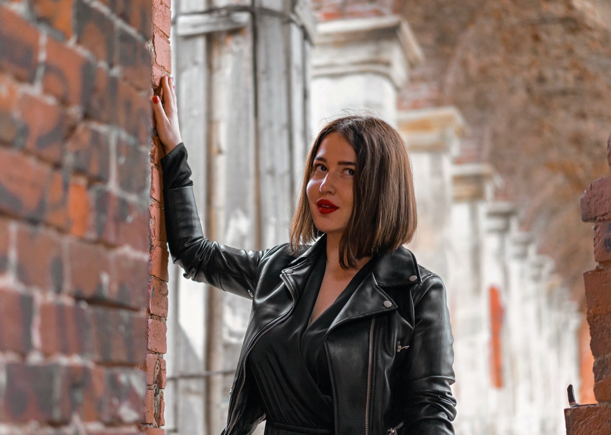 Young beautiful brunette woman in black dress posing at ancient ruins. Modern bloffer and explorer. Travelling on weekends. Gothic autumn concept.