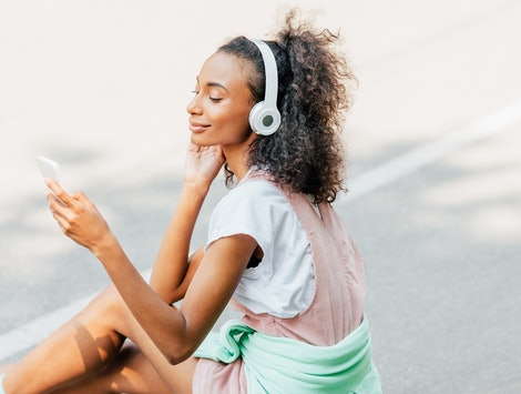 smiling african american girl listening music in headphones and using smartphone on road