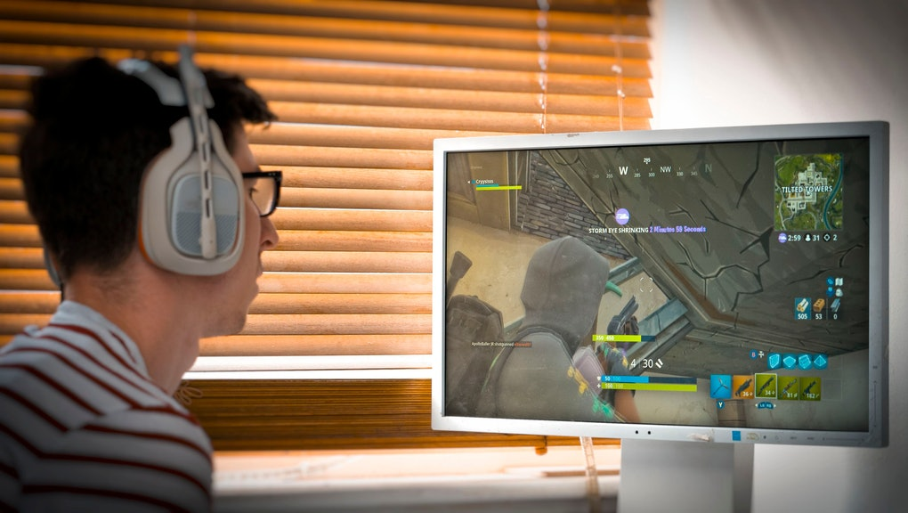 Teenager playing Fortnite video game, Fortnite is a web based multi player survival game developed by Epic Games.