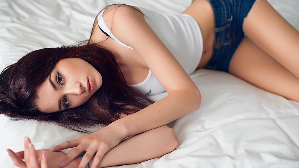 Brown-haired girl in a white top and denim shorts lying on a white bed with a gentle light portrait