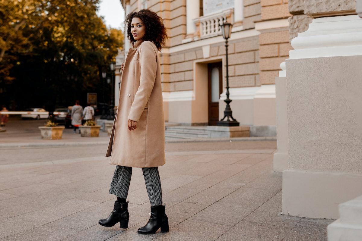 Fashion  full length  image of elegant  black woman in stylish luxury beige coat and velvet sweater,...