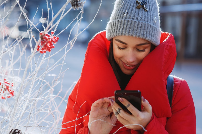 close up portrait of happy woman in red winter down jacket and knitted grey hat types text of sms or message  in her mobile smartphone standing on the winter street near traditional christmas tree.