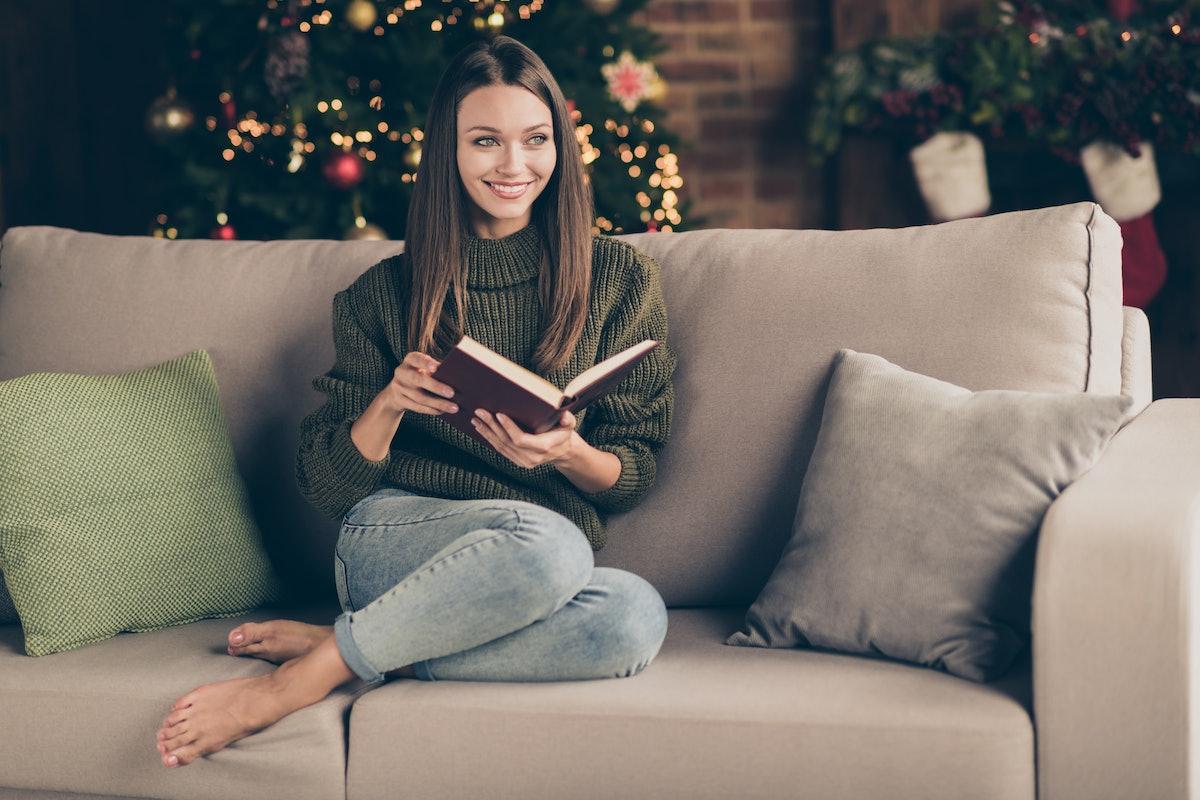 Full body photo of positive cheerful girl sit cozy divan cross her legs read christmas story imagine...
