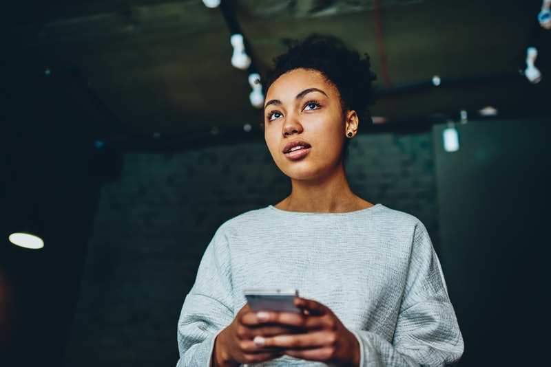 Pensive african american woman thinking about idea for blog holding mobile phone, thoughtful dark skinned hipster girl recalling password for checking updates in social networks profile using cellular