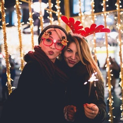 Two women dressed all festive standing in front of a row of Christmas lights outside in the winter.