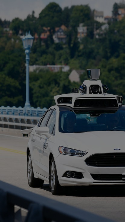 Uber employees test a self-driving Ford Fusion hybrid car, in Pittsburgh. Uber said that passengers ...