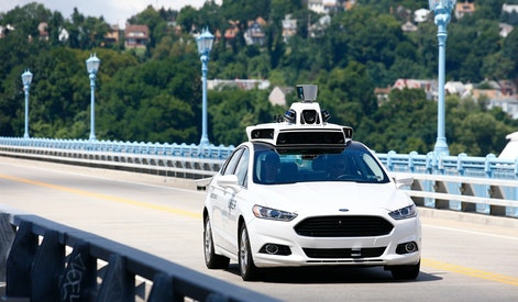 Uber employees test a self-driving Ford Fusion hybrid car, in Pittsburgh. Uber said that passengers in Pittsburgh will be able to summon rides in self-driving cars with the touch of a smartphone button in the next several weeks. The high-tech ride-hailing company said that an unspecified number of autonomous Ford Fusions with human backup drivers will pick up passengers just like normal Uber vehicles. Riders will be able to opt in if they want a self-driving car, and rides will be free to those willing to do it, spokesman Matt Kallman said