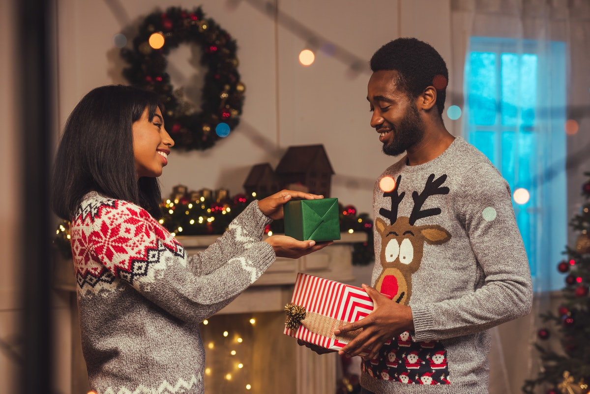 smiling african american couple presenting gifts to each other while celebrating christmas at home