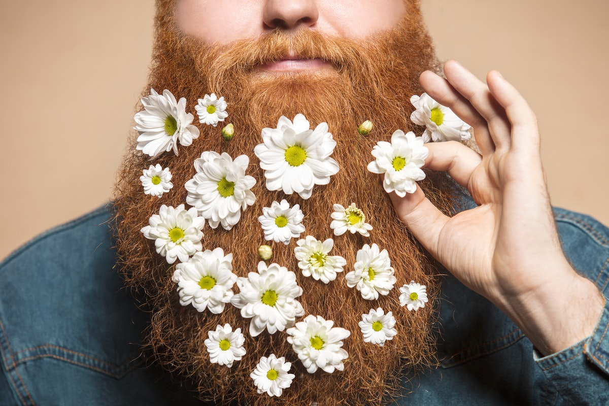 man who grew a beard decorates his facial hair with flowers