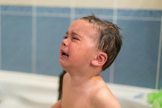 Crying baby boy in the bathtub