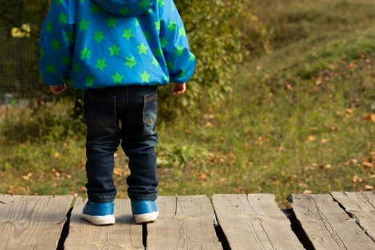 Child back side, blue shoes, clothes with gold stars, wood boards, green background