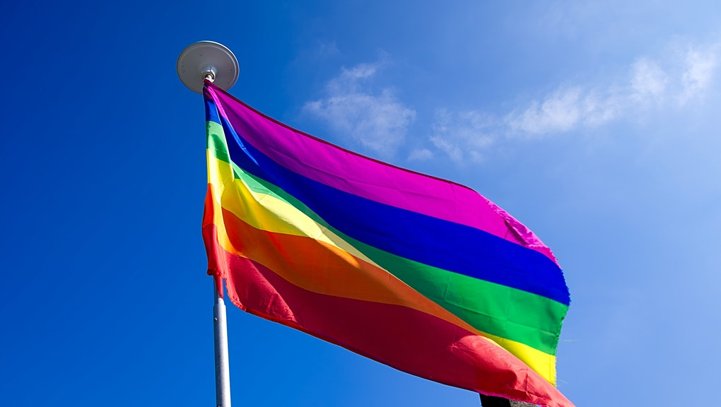 Rainbow flag on blue sky background.LGBT flag ,gay flag,gay pride.Gay flag Uk.Gay flag covering vertical chimney ,funny phallic symbol,second bottom.Humorous,non offensive view of gaycauture.