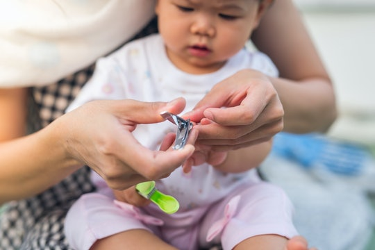 baby is cut fingernails by her mother. she concentrate at her nail.