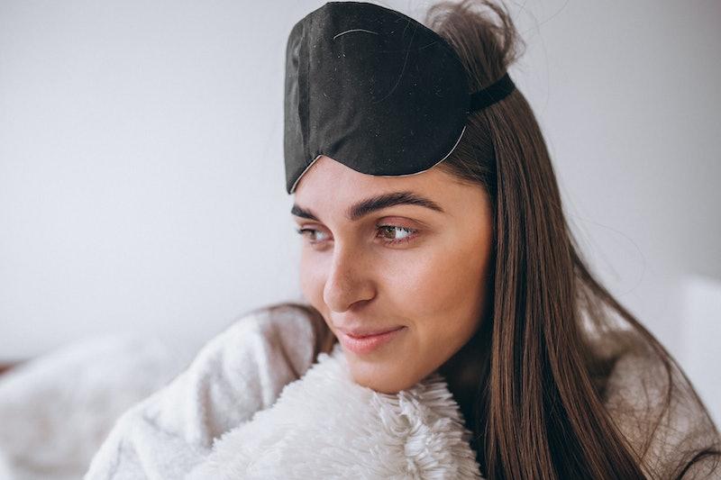 Woman in bed wearing sleeping mask