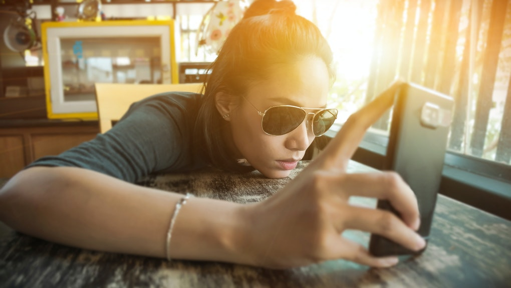 Asian woman is holding her smartphone with feeling of sadly, lonely,and confusingly.Locating on the vintage style of coffee shop on evening in Thailand