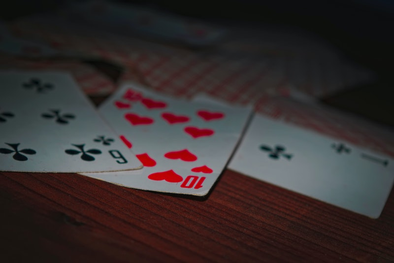 Old playing cards on wooden background close-up