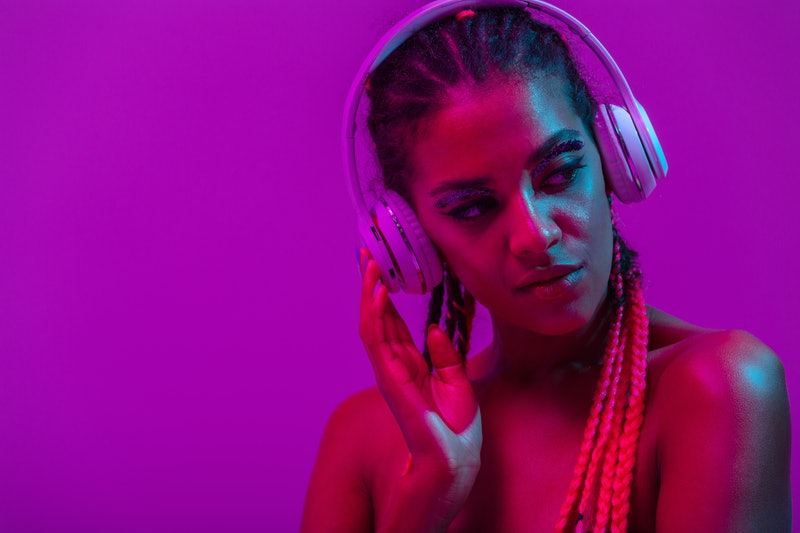 Close up beauty fashion portrait of an attractive young topless african woman wearing dreadlocks standing isolated over purple background, listening to music with headphones