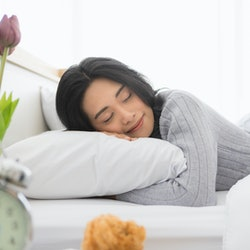 Young woman is asleep in bed. A newly discovered gene shows why some people need less sleep than others.