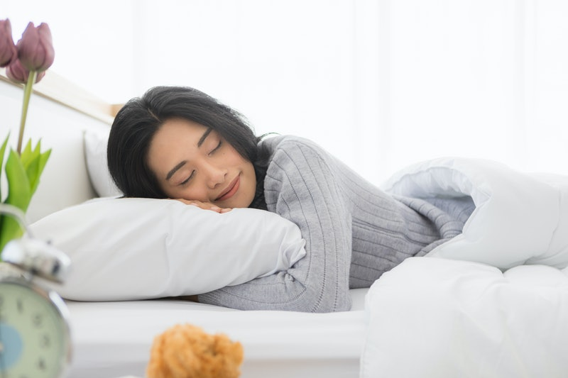 Young woman is asleep in bed. A newly discovered gene shows why some people need less sleep than oth...