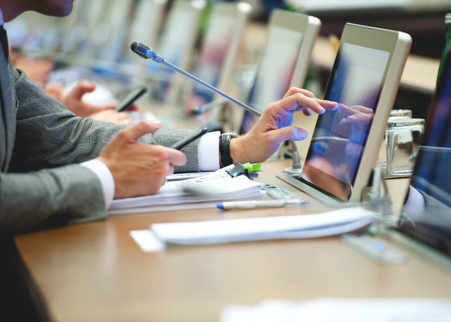 Conference room or seminar meeting room in business event. Session of Government. Business man finger touching screen on tablet pc. working in modern bright office while type your text