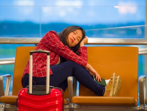 lifestyle portrait of young pretty tired and exhausted Asian Korean tourist woman in airport sleeping bored sitting at boarding gate hall waiting for delayed or canceled flight