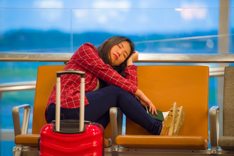 lifestyle portrait of young pretty tired and exhausted Asian Korean tourist woman in airport sleepin...