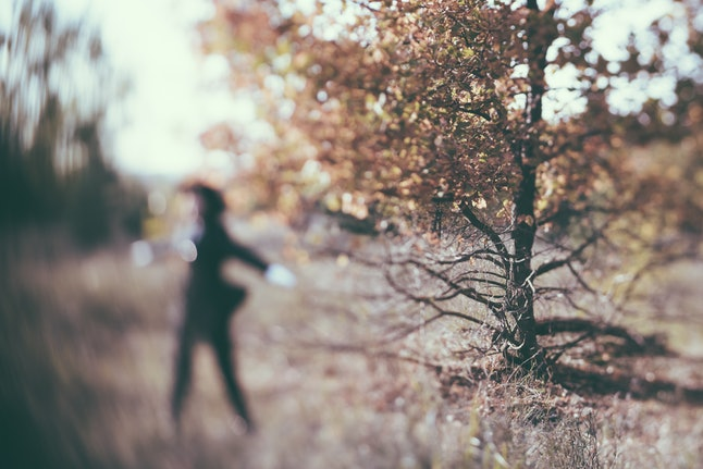 Woman in a black suit and a black hat dancing a weird witchy dance in the autumn sunset forest. Unusual focus