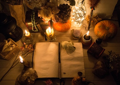 An old book with clean pages and burning candles, witchcraft, natural crystals and skull, pumpkin, wicca, halloween