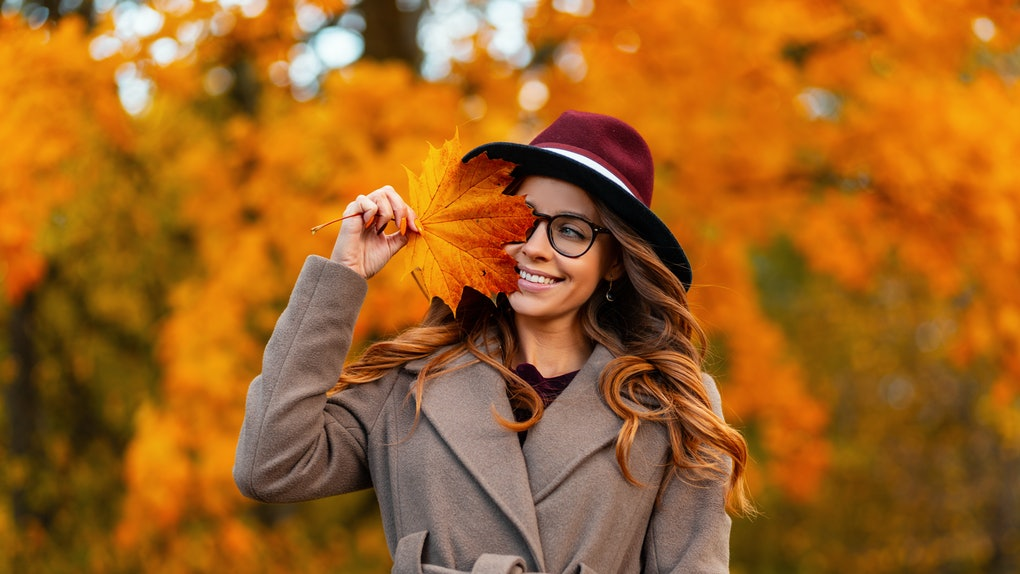 Happy trendy young woman in glasses in a vintage hat in an elegant coat poses with an orange-yellow autumn leaf outdoors in a park. Joyful girl with a cute smile holds a golden maple leaf near face.